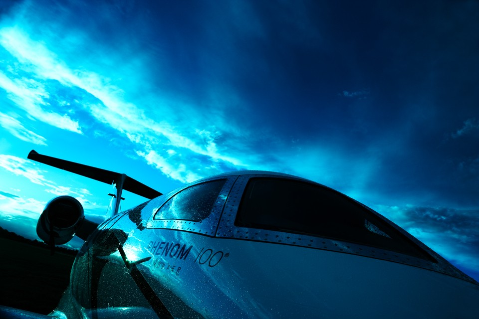 Embraer Phenom 100 business jet in dramatic light.
